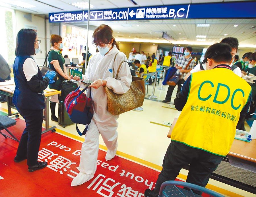 隨著新冠肺炎疫情趨緩,旅客入境台灣是否逐步解禁有待觀察,1名身穿防護衣的旅客,20日在桃園機場查驗健康聲明書後,準備入境台灣。(范揚光攝)