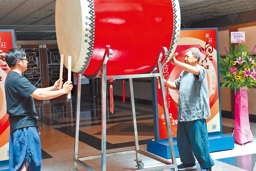 新莊文化藝術中心21日起展出「新莊(口向)仁和鼓文化特展」,製鼓大師王錫坤(右)與兒子王凱正(左)聯手擊鼓,為活動揭開序幕。(許哲瑗攝)