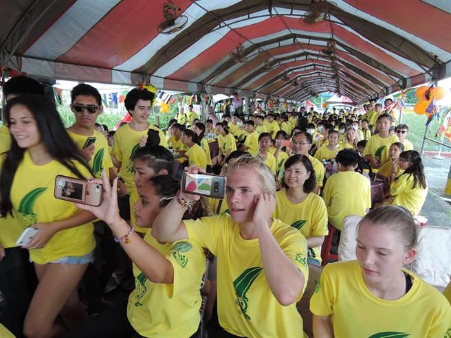 學員看著台上家政媽媽的舞蹈表演,興奮地拿起手機記錄。(張毓翎攝)