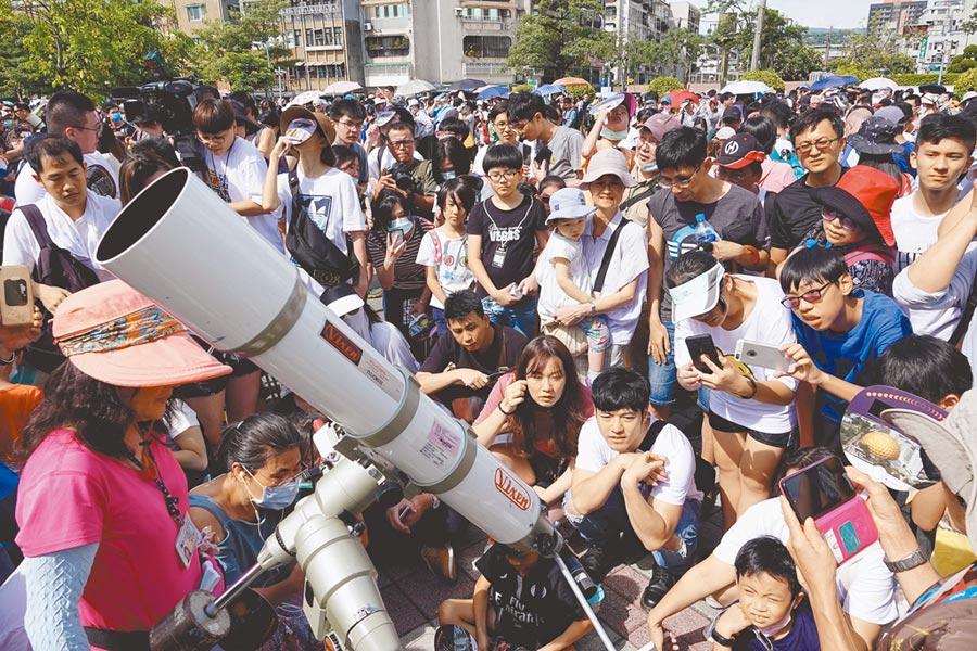 北台灣因緯度僅可見日偏食。台北市立天文科學教育館舉辦觀測活動,吸引數千人到場參加,民眾透過望遠鏡觀測日食投射影像。(黃世麒攝)