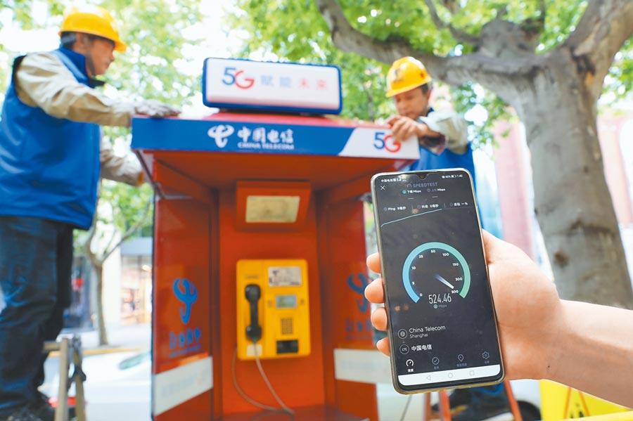 5月15日,上海街頭,中國電信工作人員在電話亭安裝5G微基地台。(中新社)