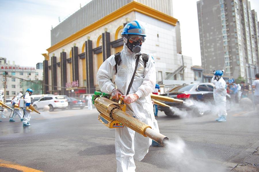 6月16日,北京藍天救援隊隊員在岳各莊批發市場展開消毒作業。(新華社)
