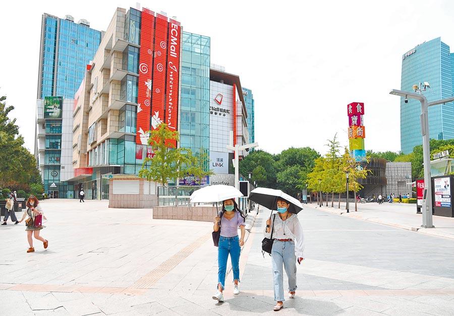 6月8日,北京市中關村步行街,行人用遮陽傘遮擋陽光。(新華社)
