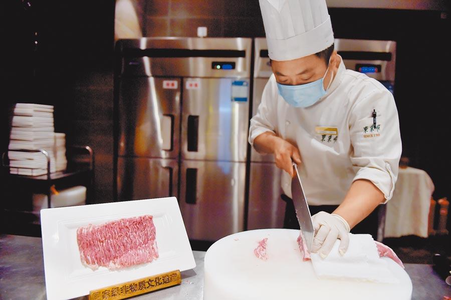 6月14日,北京一家餐廳廚房內,廚師在切羊肉。(新華社)