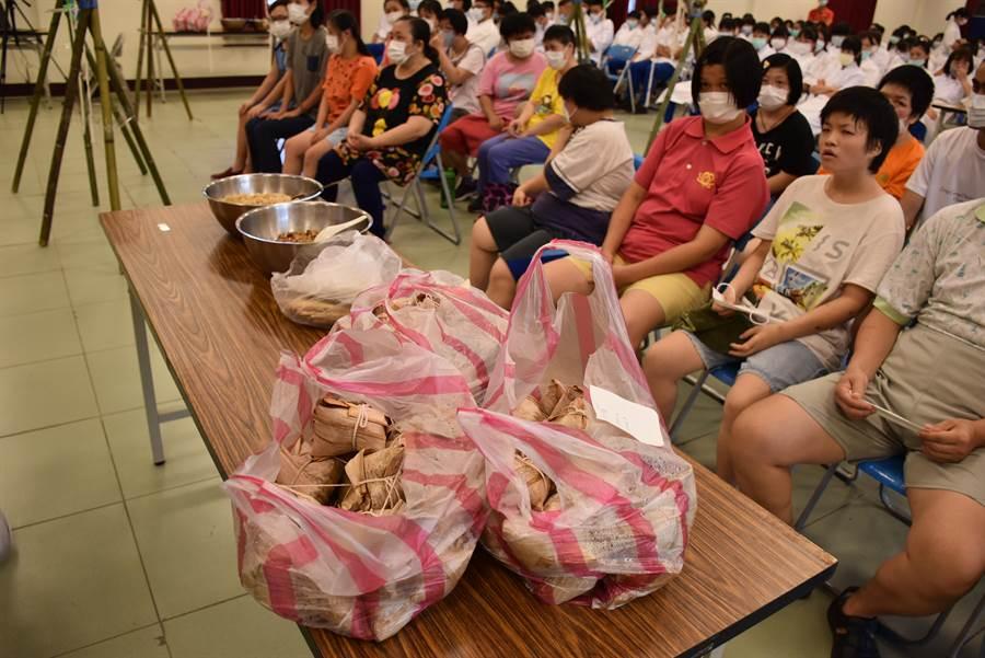 竹南中興商工餐飲科同學,23日上午一起包粽子送暖給聖家啟智中心小朋友。(謝明俊攝〕