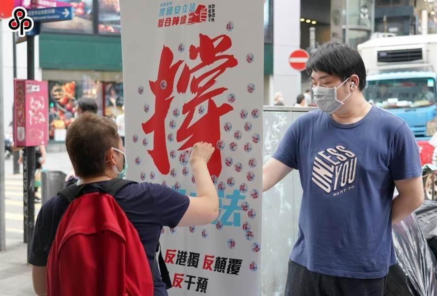 香港教育局長稱將向學生宣傳和教育國安立法重要意義。圖為5月29日「香港各界撐國安立法聯合陣線」在中環街頭設街站舉行「撐國安立法」簽名活動。(中新社)