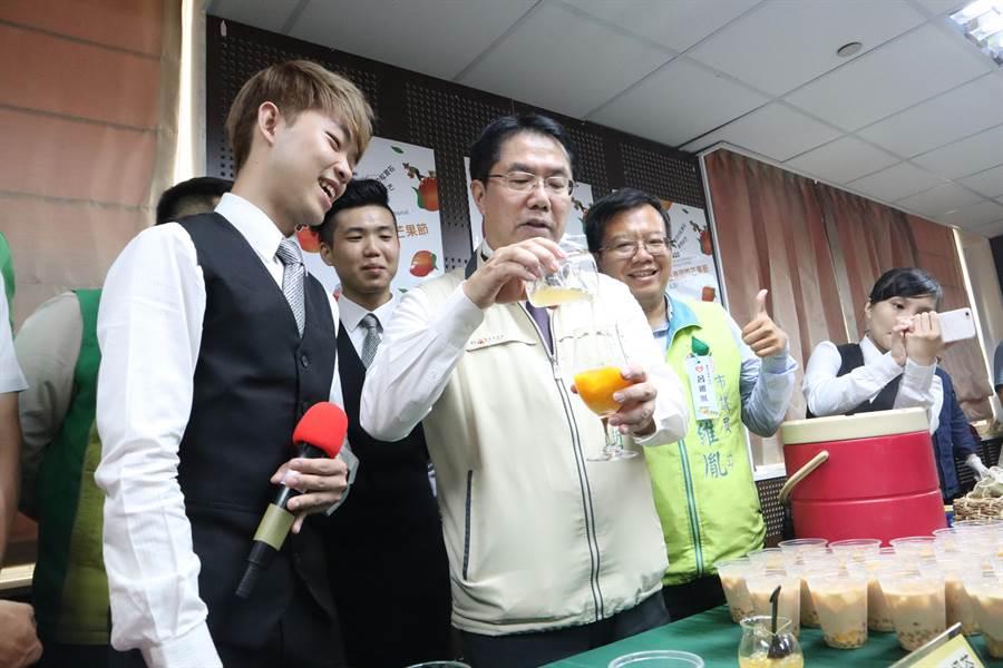 台南市長黃偉哲(前排左二)23日下午參加宣傳記者會,現場調配清涼消暑的芒果珍珠奶茶。(李宜杰攝)