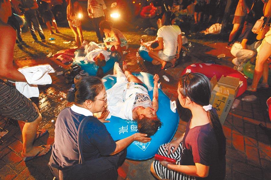 5年前八仙樂園發生粉塵爆炸意外,造成超過上百位民眾燒燙傷送醫急救。圖為當時現場民眾用游泳圈充當擔架救人。 (本報資料照片)