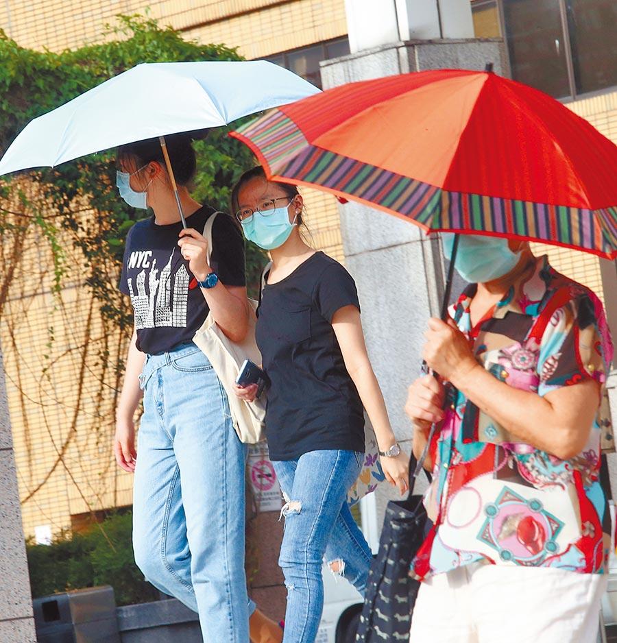 中央氣象局針對北北基、南投縣、宜花東等7縣市發布高溫特報,許多外出民眾紛紛自備傘具,抵擋高溫。(陳信翰攝)
