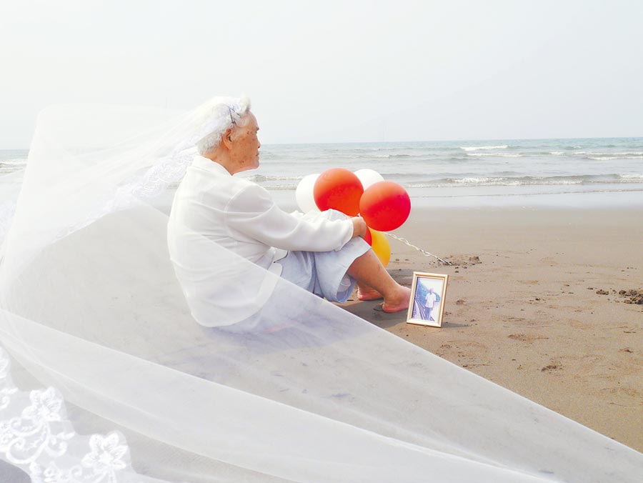 「這是我第一次看到海!」88歲詹奶奶生活在山城中,大湖日照中心團隊得知奶奶畢生看海心願,眾人齊心設計規畫圓夢之旅,帶著詹奶奶到海邊體驗海水清涼,更在絕美海景中,披上浪漫白紗,與丈夫遺照拍下美麗的婚紗照。(大湖日照中心提供)