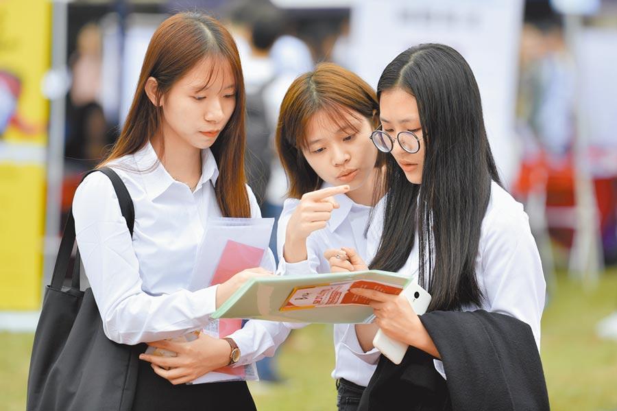 華南理工大學學生在畢業生供需見面會上研究職位資訊。(中新社資料照片)