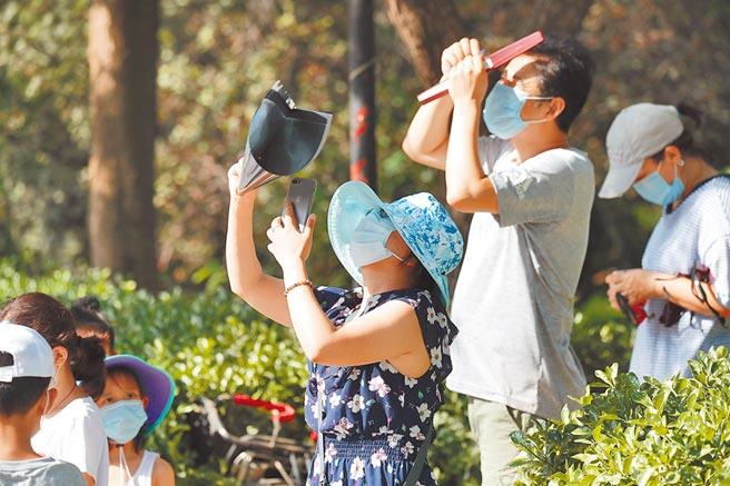 北京未封城,民眾仍可自由外出,圖為6月21日,北京市民在小區裡觀賞日食。(中新社)