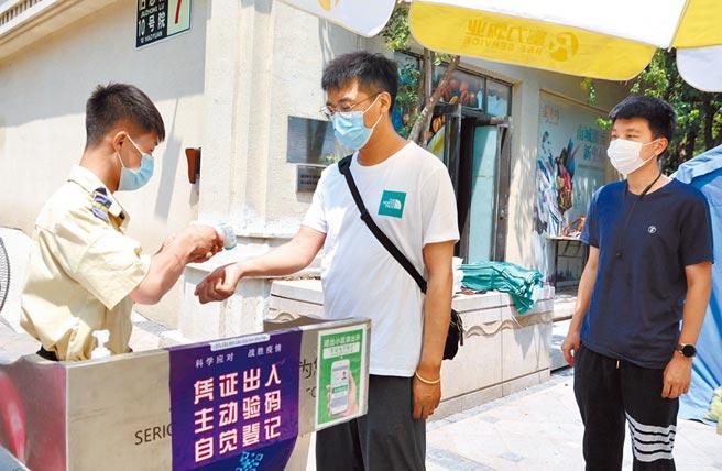 北京全力抗疫,圖為6月21日,北京市大興區舊宮鎮的居民測量體溫進入小區。 (新華社)