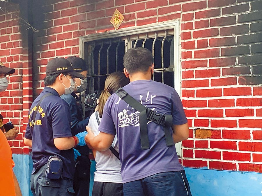 林婦(中)隔著鐵窗凝望不幸葬身火窟的兒女和丈夫遺體,當場痛哭。火調人員現場進行採證,初步研判起火點在客廳。(曹婷婷攝)