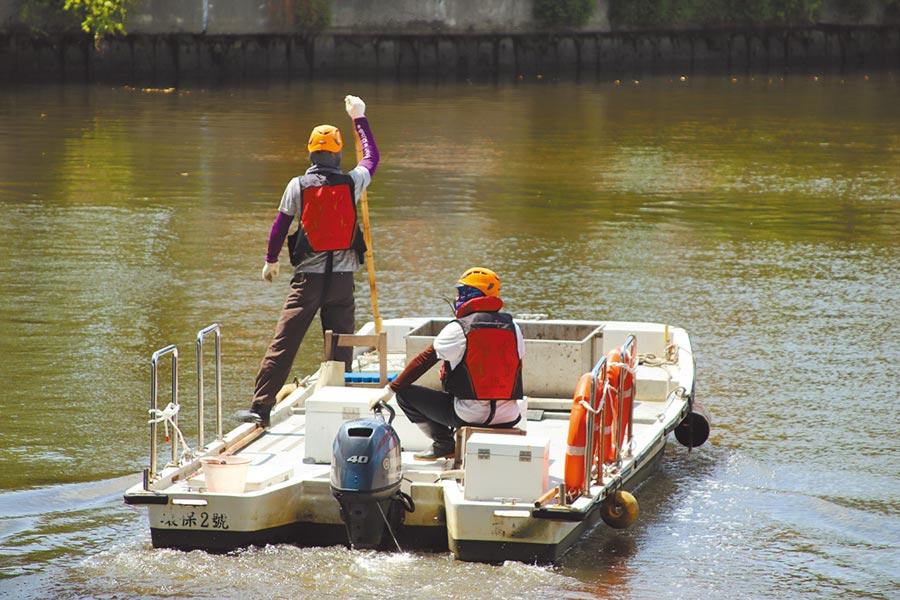 因不排除還有其他屍袋漂流於愛河中,清潔人員23日中午持續駕駛小艇巡視打撈。(洪浩軒攝)