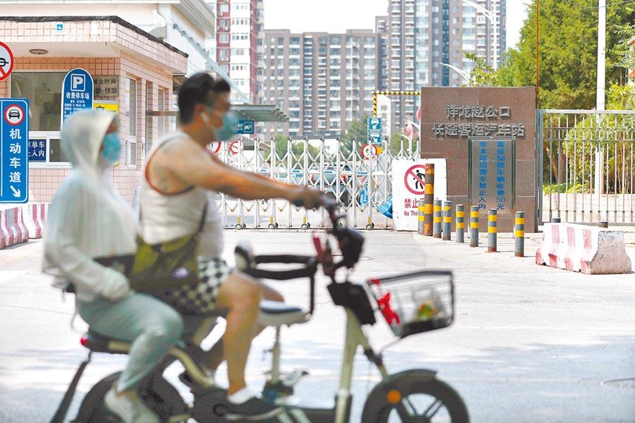 北京市自6月19日起,省際客運班線全部停運,圖為民眾從北京趙公口長途客運站門前經過。(中新社)