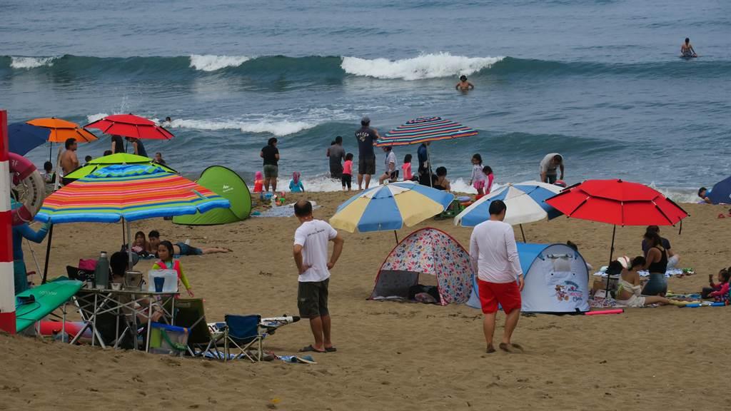 天氣炎熱,民眾選擇到海邊消暑,金山中角灣遊客數在連假首日成長達3倍之多。(張睿廷攝)