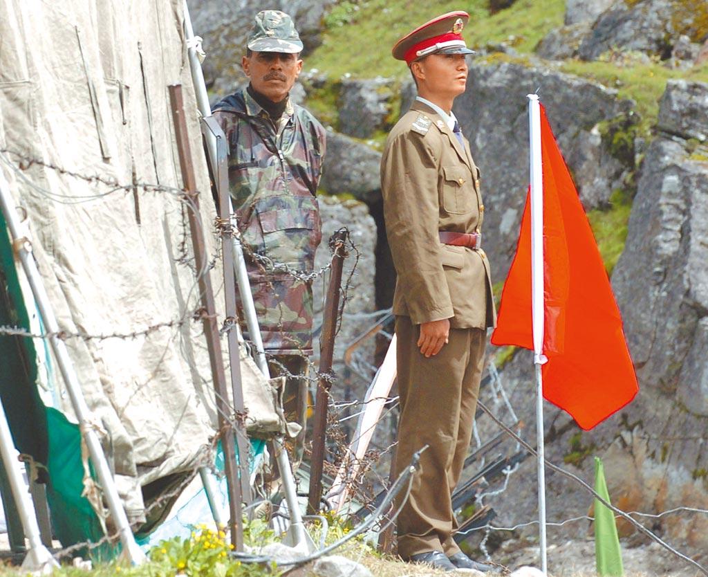 中印邊境乃堆拉山口,一名中國邊防軍人(右)與一名印度邊防軍人隔著邊界的鐵絲網值勤。(新華社資料照片)