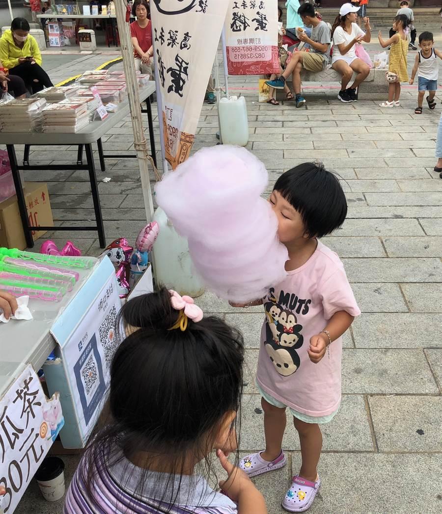 特色市場吸引人潮,一位小朋友正專心吃著棉花糖。(李金生攝)