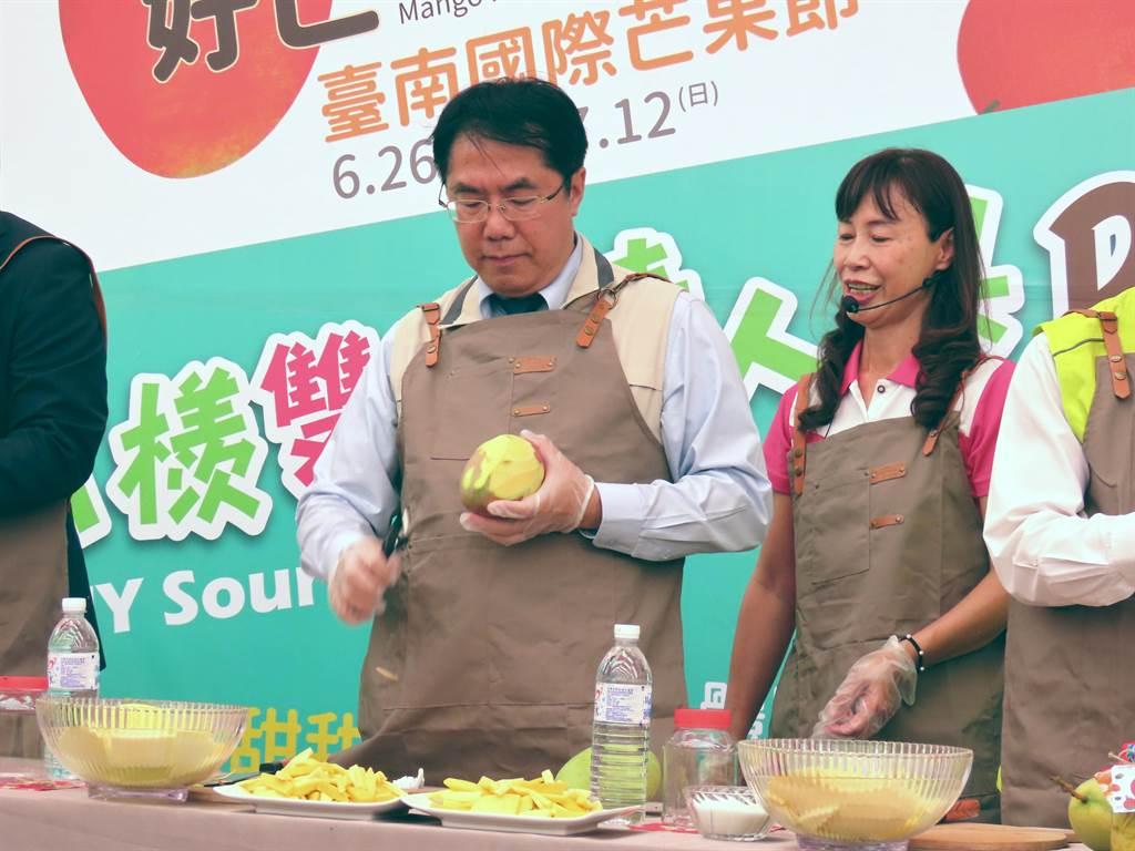 台南市長黃偉哲動手DIY芒果青,削皮動作俐落。(莊曜聰攝)