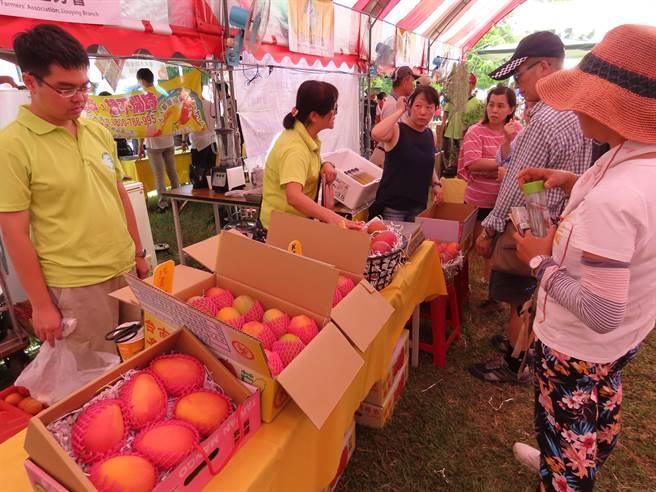 芒果節開幕現場有農特產展售,遊客採買新鮮芒果。(莊曜聰攝)
