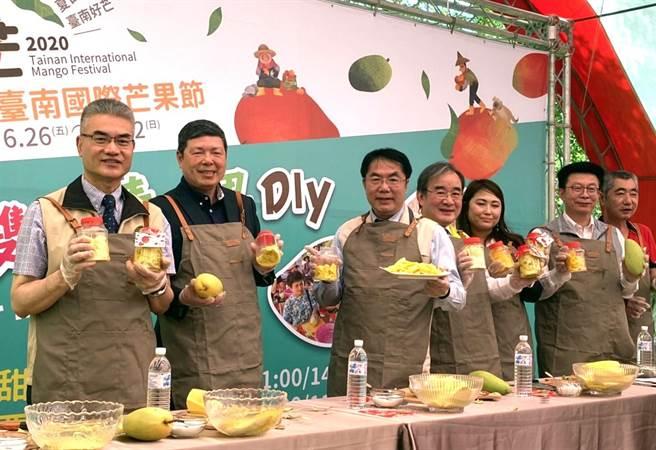 南國際芒果節邁入第8年,26日開幕活動在大內區走馬瀨農場舉行,台南市長黃偉哲(左三)體驗用玉文芒果手做芒果青,與端午連假前來的遊客同樂。(莊曜聰攝)