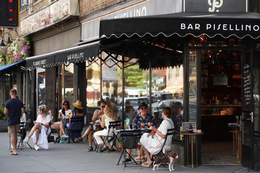 包括紐約州、新澤西州、德州等數個州經過數周的經濟重啟後,單日確診人數又創新高,被迫緊急叫停,把民眾從街頭趕回家中,有些州甚至對來自疫情嚴重州的民眾進行強制隔離。圖為紐約市露天咖啡座享受悠閒時光的市民。(圖/路透)