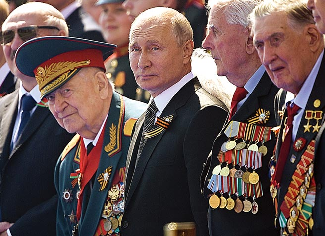 俄羅斯總統普丁(中)24日出席在莫斯科紅場舉行勝利日閱兵典禮,並與二戰老兵站在一起觀看部隊分列式。俄羅斯正在進行修憲公投,一旦通過,普丁可以再次投入總統選舉。(美聯社)