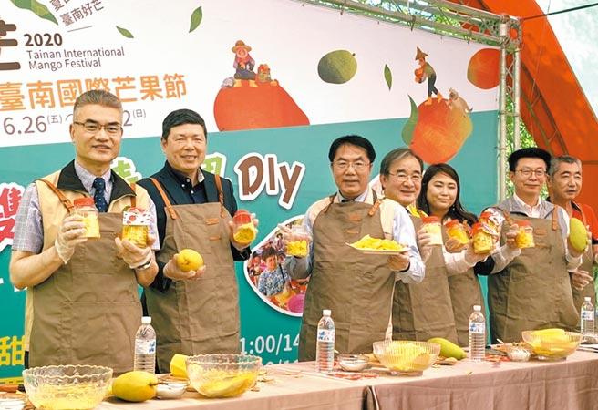 台南國際芒果節26日在走馬瀨農場舉行開幕活動,台南市長黃偉哲(左三)體驗做芒果青。(莊曜聰攝)