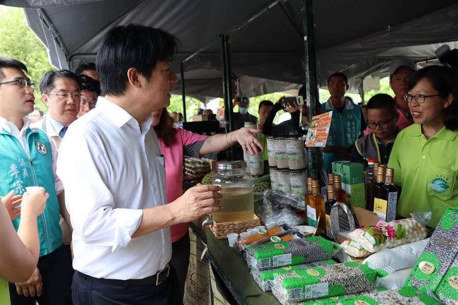 賴清德副總統27日上午到國道東山休息站參加白河青農的蓮子季推廣活動,向遊客推銷白河蓮子。(劉秀芬攝)