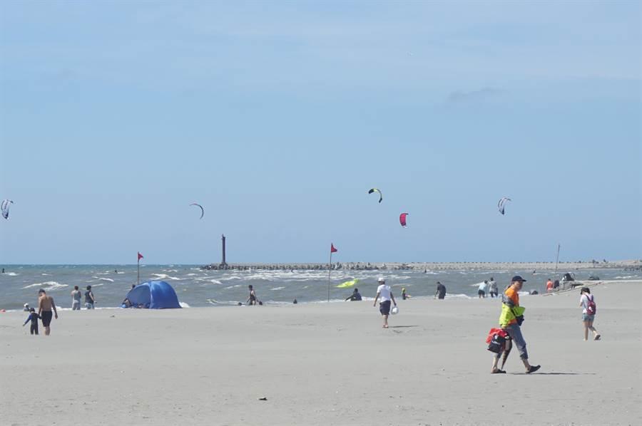 大安海水浴場遊客如織,大小朋友開心戲水,還有風箏衝浪玩家在海上挑戰騰空翻躍,熱鬧滾滾。(王文吉攝)