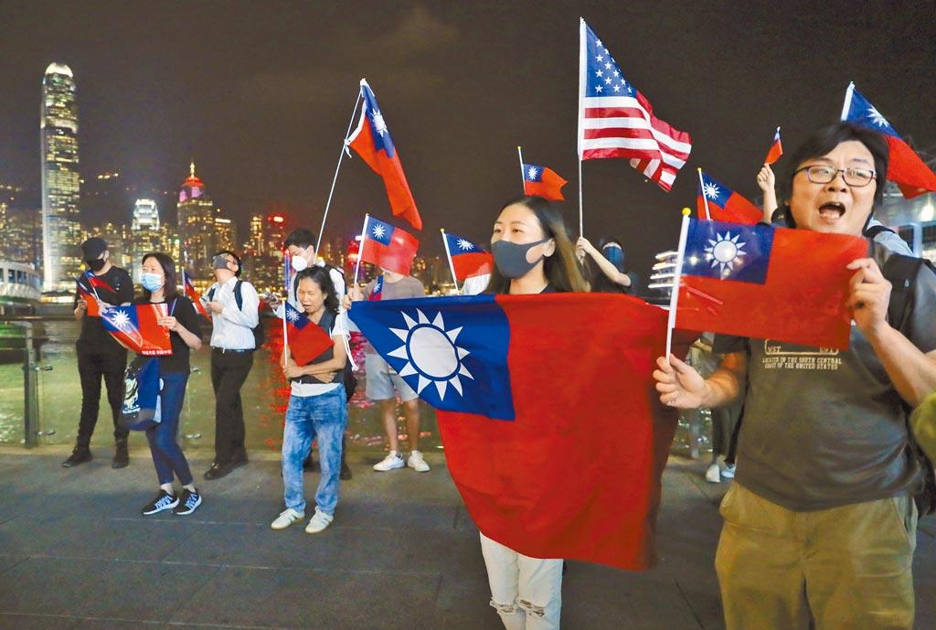 去年10月10日,參加反送中遊行的民眾在香港尖沙咀地區高舉美國星條旗和中華民國國旗。港版「國安法」若通過,在香港公開揮舞美國、英國、港獨乃至青天白日滿地紅旗幟,將被視為勾結境外勢力,牴觸國安法。(美聯社)