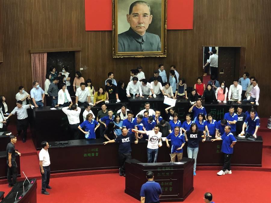 國民黨團全被拉下主席台,但仍在議場內舉標語抗議表達訴求。(圖/廖映翔攝)