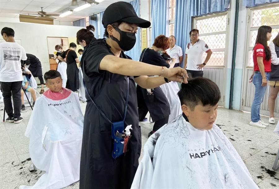 知名生技公司與髮廊合作,在畢業季前到來偏鄉小校為學生義剪,送出別開生面的畢業禮物。(林和生攝)