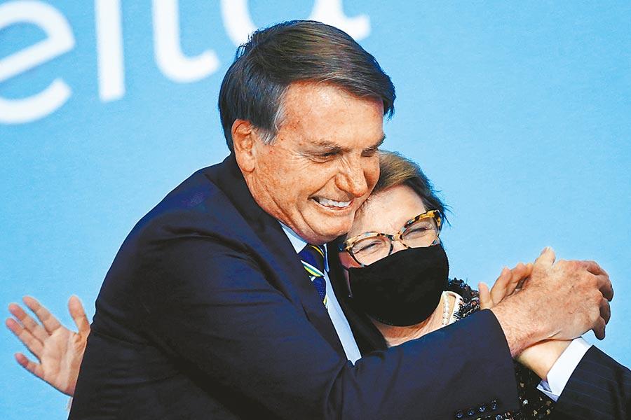 巴西總統波索納洛先前參加政治集會時,經常違反社交距離規定,與民眾握手、擁抱。(路透)