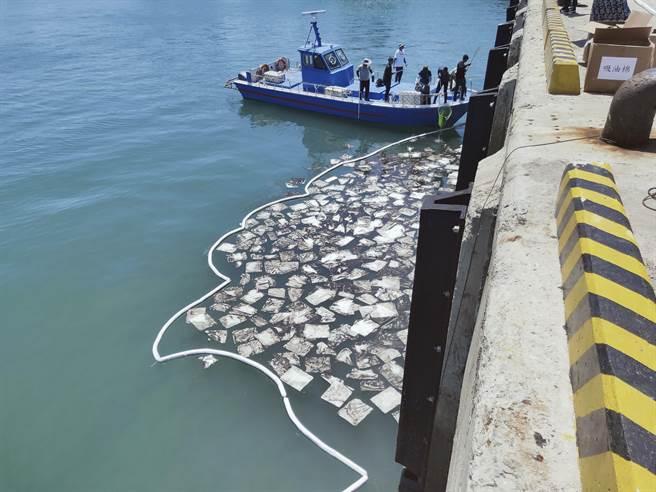 安檢所幹員使用吸油棉除汙,並移除汙染廢棄物,轉交環保局人員攜回處置。(岸巡提供)