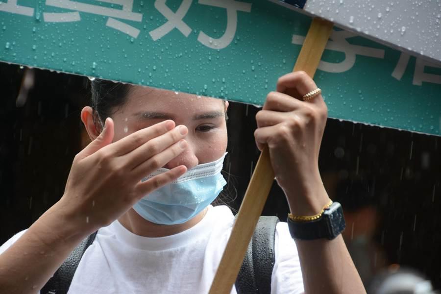 掃街過程中一度下起大雨,李眉蓁團隊年輕工作人員不畏風雨,盡責舉牌任由雨滴打在臉上。(林宏聰攝)