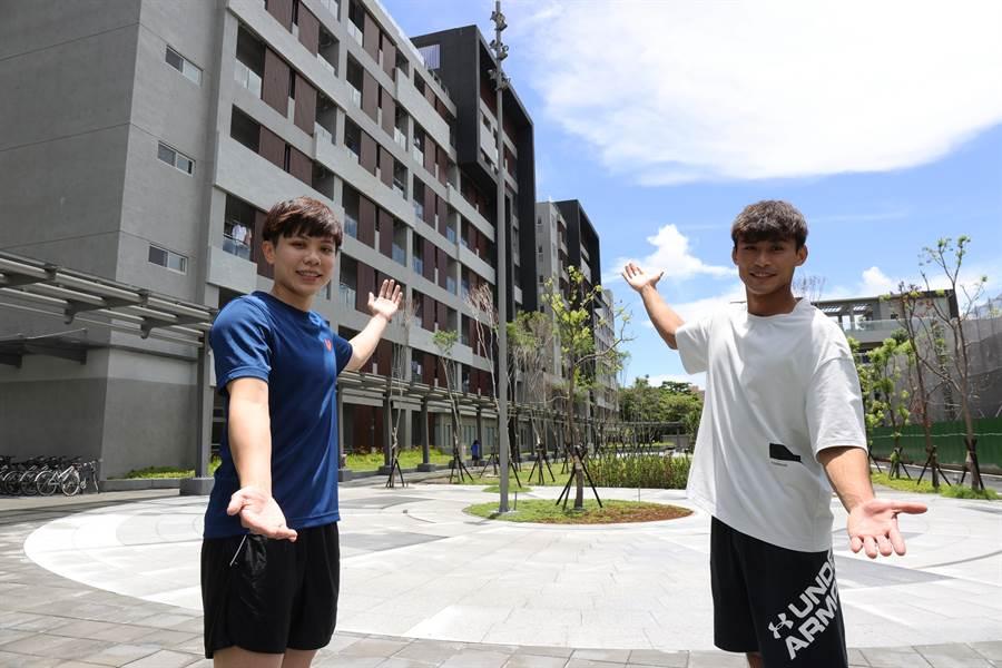 桌球女將鄭怡靜(左)和柔道男將楊勇緯(右)和宿舍大樓合照。(國訓中心提供)