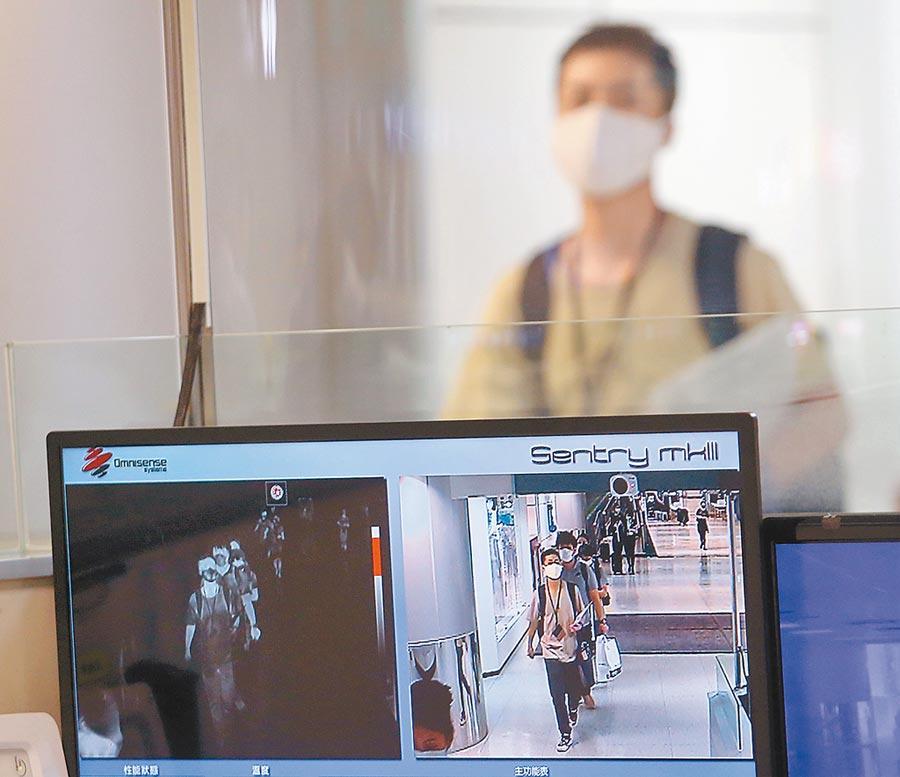 學者呼籲應盡速做入境普篩。圖為旅客入境台灣,走過發燒篩檢站。(本報資料照片)