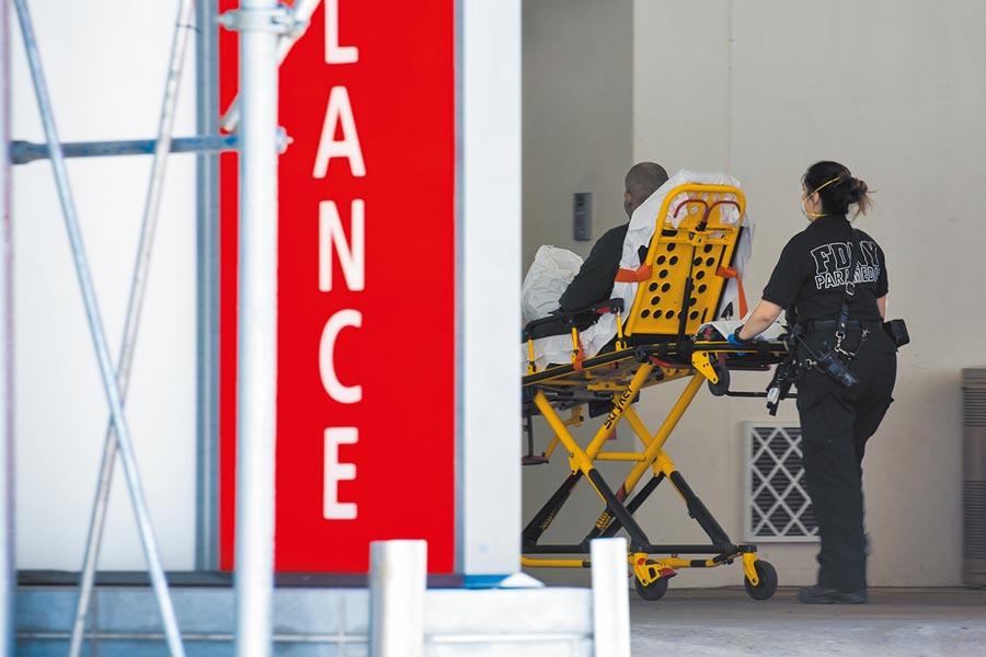 5月26日,美國紐約的醫護人員將一名新冠肺炎患者送入急診室。(新華社)