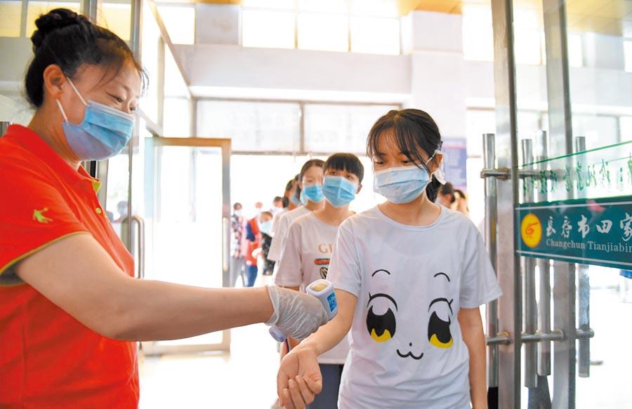 大陸考生考場戴不戴口罩將視情況而定,圖為長春市高考生戴口罩在防疫演練中接受體溫檢測。(新華社)
