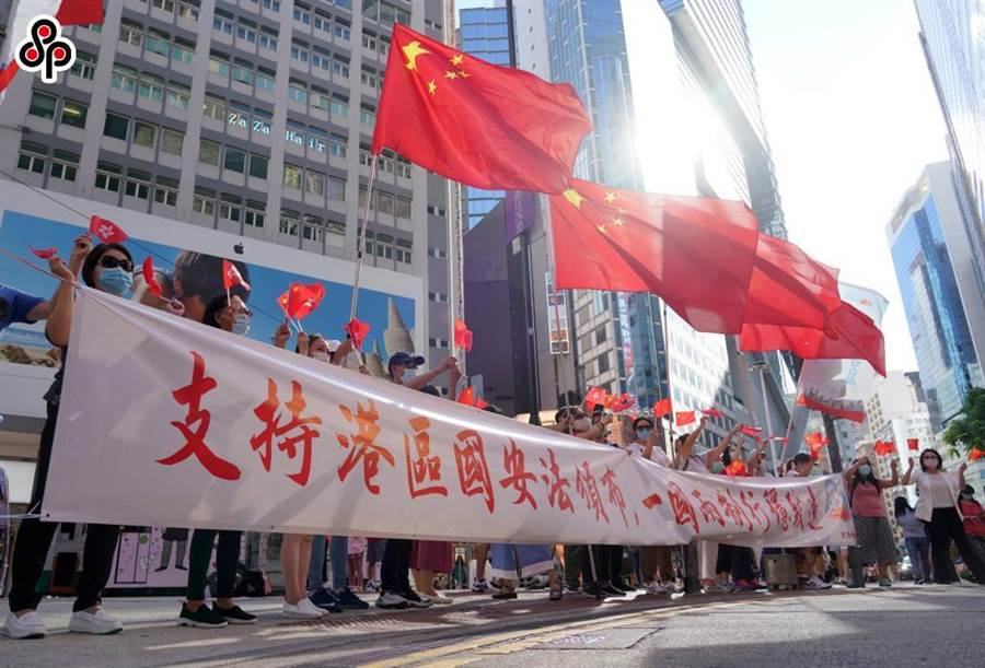 《環時》社評指港版《國安法》配備利齒,同時鼓勵向前看。圖為6月30日下午香港市民在銅鑼灣街頭舉行「支持港區國安法唱國歌」活動。(中新社)