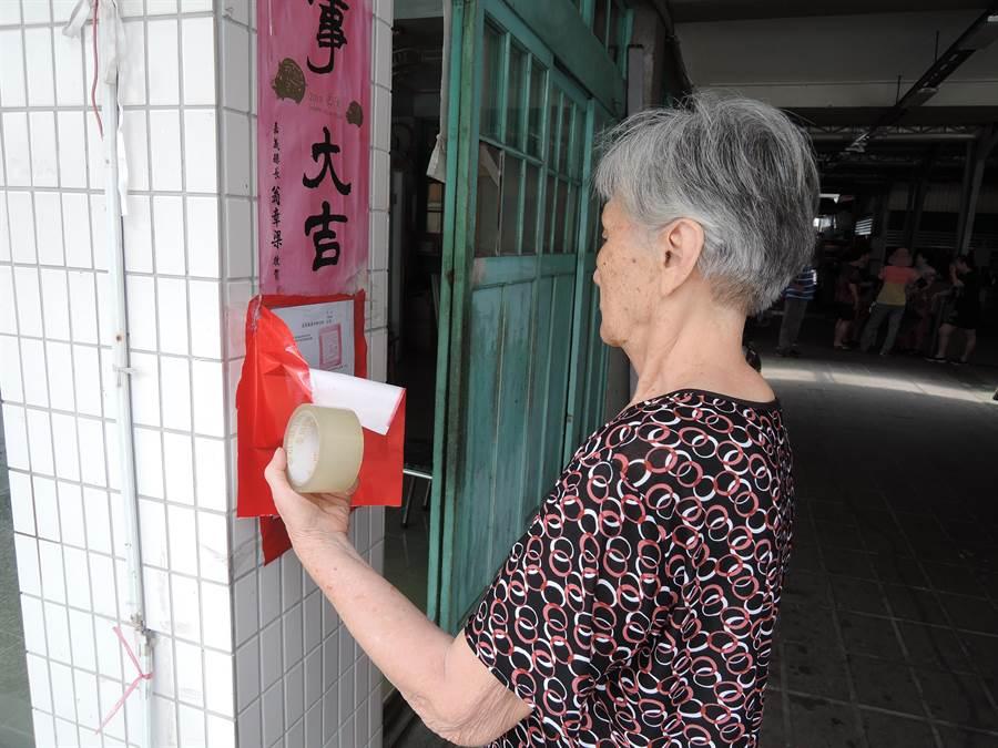 一名住戶拿紅紙、膠帶覆蓋市場內所有的公告。(張毓翎攝)