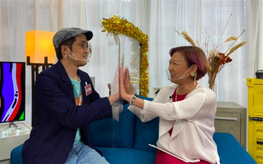 網紅Iku老師(左)與龍羽老師各坐隔板兩邊即興演起「龍羽探監」,逗笑全場。(國興衛視提供)