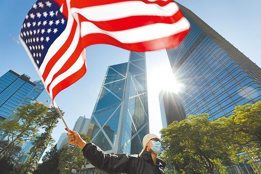 趕在港版《國安法》過關之前,美國務卿蓬佩奧6月29日搶先宣布,停止對港出口防衛產品,並將針對出口至香港的軍民兩用科技產品,實施等同大陸的貿易限制;美國商務部長羅斯同日也跟進,稱將撤銷香港特殊地位,並暫停對港關稅優惠待遇。圖為在香港一次集會中,一名抗議者揮舞著美國國旗。(美聯社)