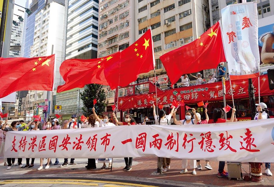 大陸人大常委會通過港版《國安法》,美國的反應可以「重重舉起,輕輕放下」來形容。圖為香港市民在銅鑼灣街頭舉行「支持港區國安法唱國歌」活動。(中新社)