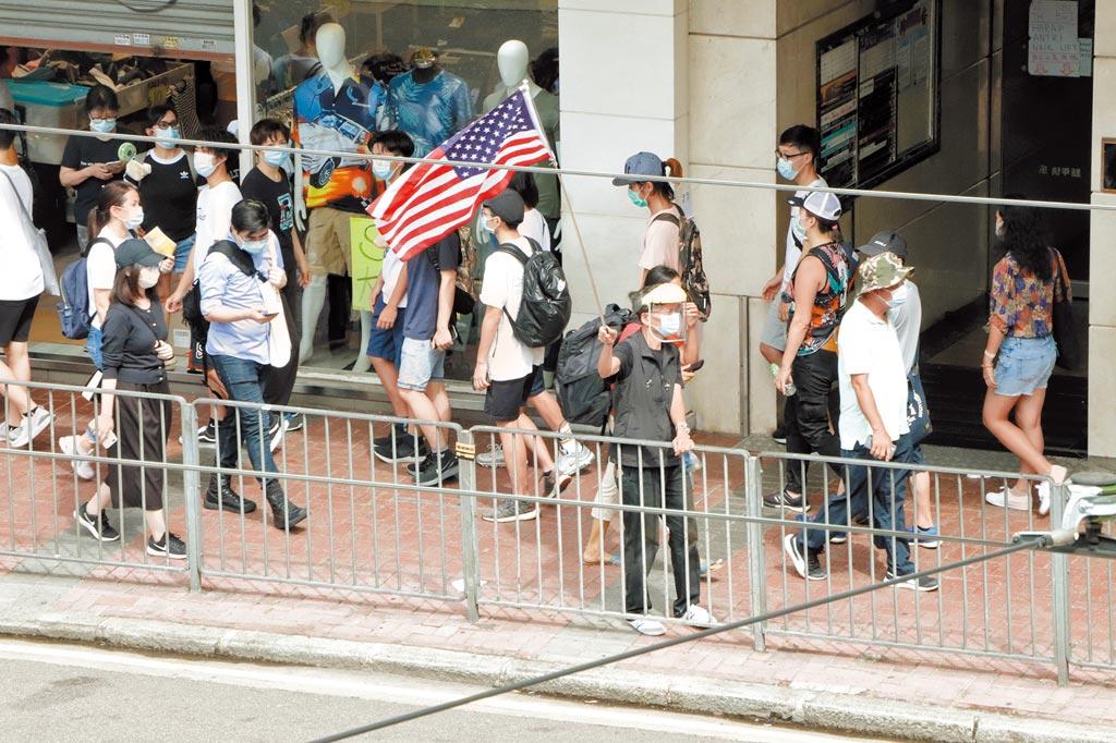 港區國安法生效後的第一個「七一」紀念日,民眾上街在銅鑼灣崇光百貨一帶等多個地點進行抗議示威,其中有人舉起美國國旗。(中央社)