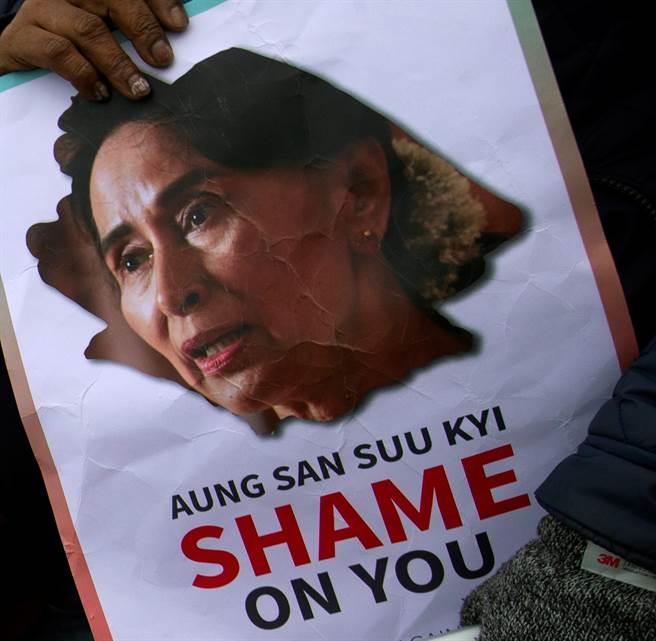 2019年12月10日世界人權日,抗議人士在國際法庭外持標語抗議翁山蘇姬。(美聯社)