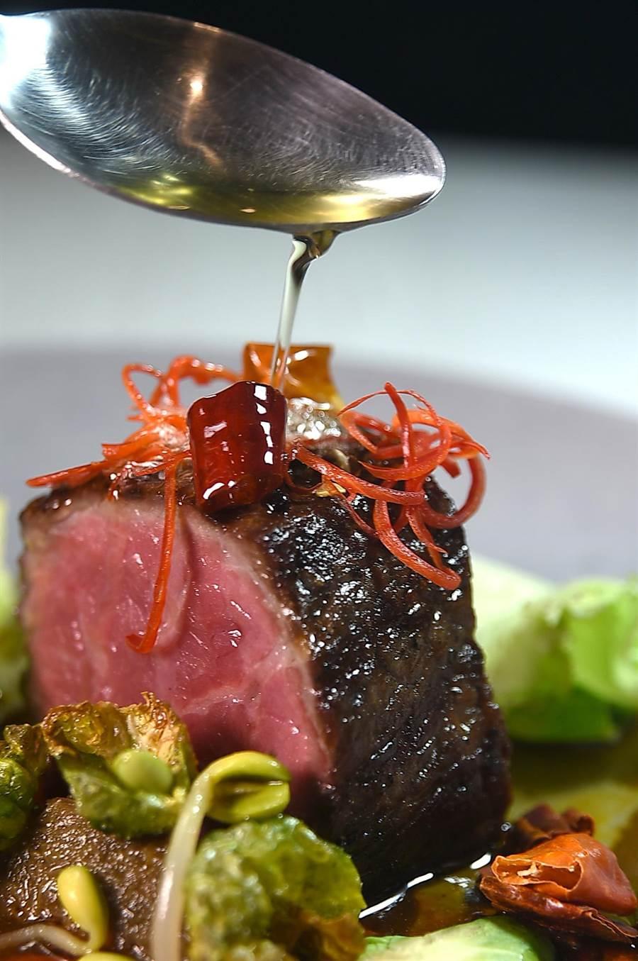 〈水煮美國特級牛排〉 是以紅油醬汁澆淋提味,熱油一接觸到牛排時會起泡冒煙。(圖/姚舜)