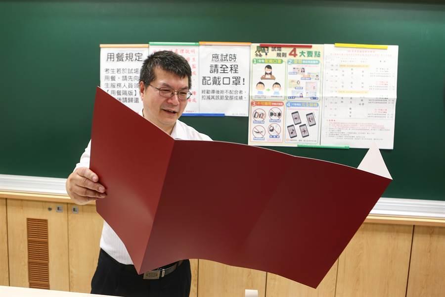 台大註冊組主任李宏森示範使用指考用餐隔板。(鄧博仁攝)